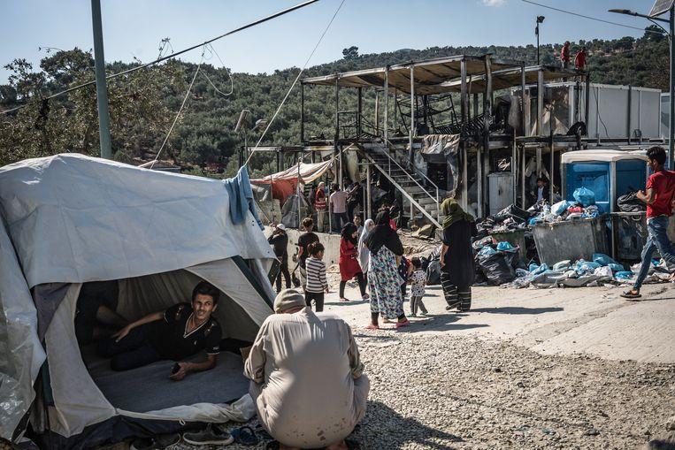 Een man in een tent naast het gebouw dat afbrandde in kamp Moria. Beeld Zolin Nicola