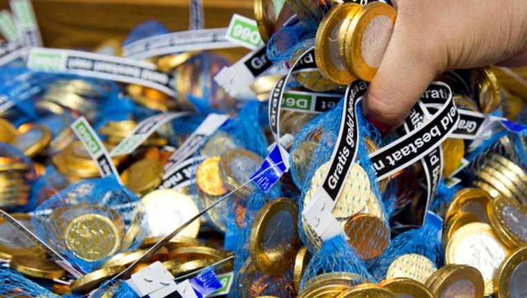 Leden van D66 delen gratis geld uit in de vorm van chocolade muntjes tijdens de eerste campagnedag van D66 voor de landelijke verkiezingen van 12 september. Beeld ANP