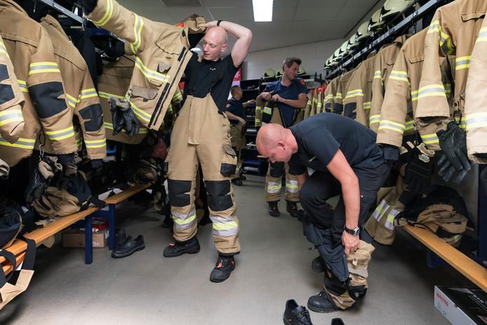 Brandweerlieden van Brandweer Brabant-Noord maken zich vliegensvlug paraat voor een uitruk. Op de voorgrond: Marijn Ekels, staand met jas: John de Graaf, achterin: Davey Hoosemans