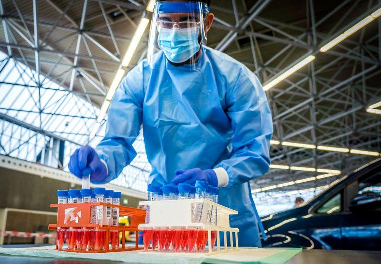 Een medewerker van de GGD Amsterdam neemt een coronatest af in een testlocatie bij de RAI. Beeld Hollandse Hoogte /  ANP