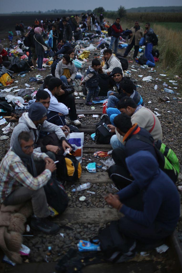 Migranten wachten op een spoor in Hongarije tot ze worden verplaatst. Beeld getty