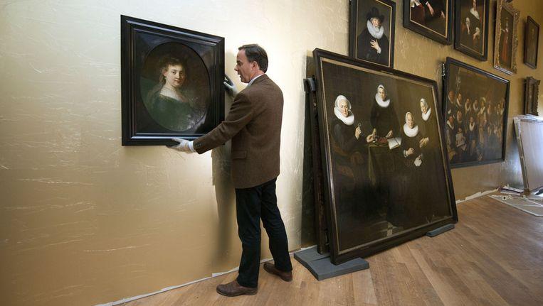 Conservator schilderijen Norbert Middelkoop hangt in 2011 een door Rembrandt geschilderd portret van Saskia van Uylenburgh op tijdens de verbouwwerkzaamheden in het Amsterdam Museum. Beeld anp