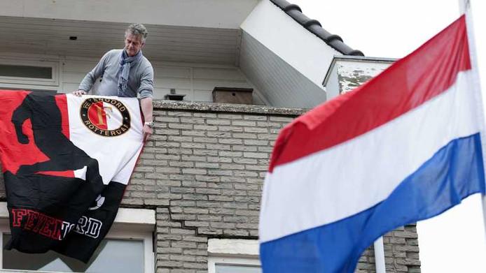 Een Feyenoord-fan hangt de vlag uit voor de zeven geselecteerde Feyenoord-spelers tegenover Huis ter Duin waar de spelers van het Nederlands elftal zich verzamelen ter voorbereiding op de WK kwalificatiewedstrijd tegen Estland.