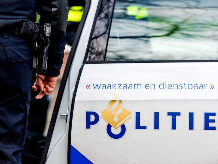 2015-01-22 12:54:29 GRONINGEN - Een politieagent op straat naast een politieauto. ANP XTRA KOEN VAN WEEL