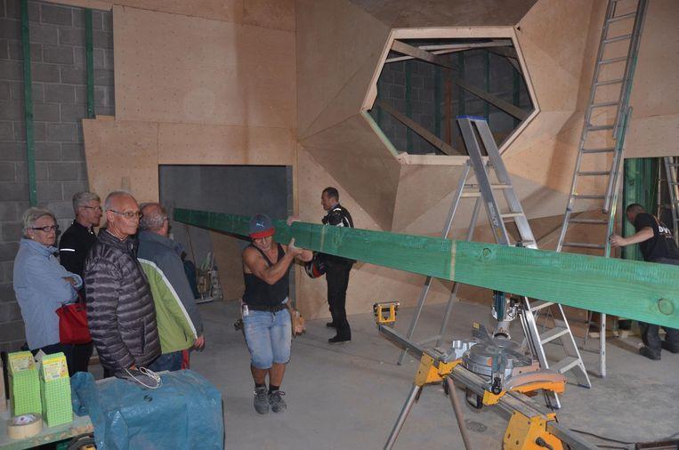 Bezoekers krijgen een rondleiding terwijl een arbeider een balk binnendraagt in de nieuwe klimzaal.