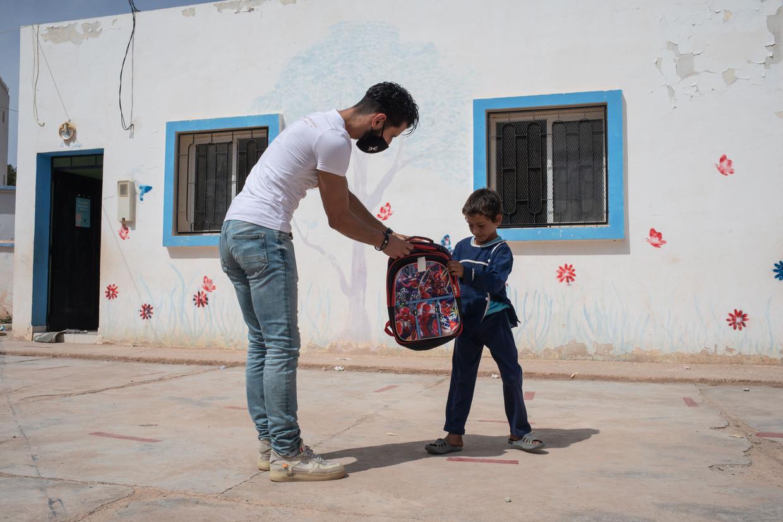 Karim Boulidam uit Utrecht geeft in een plaatsje in het Rifgebergte schooltassen weg aan kinderen. Nu de meeste Europese Marokkanen hun vakantie niet doorbrengen in het land waar hun familie woont en er dus geen geld uitgeven, heerst er armoede.  Beeld César Dezfuli