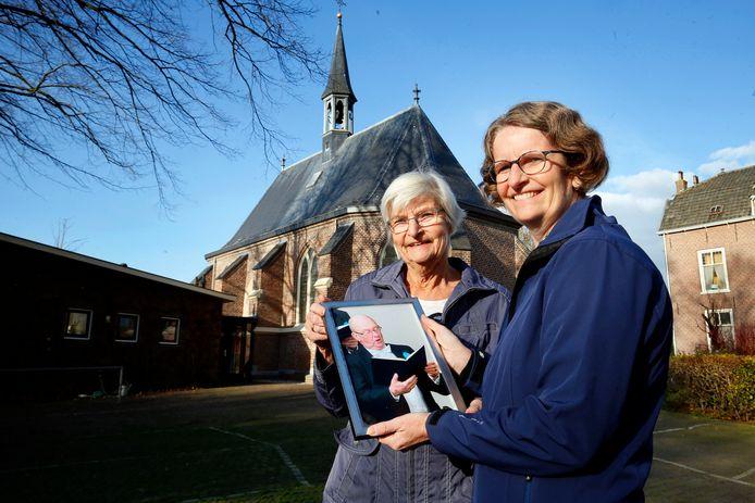 Joke Huisman en Esther Hijman bij het kerkje van Sleeuwijk met een foto van hun overleden man en vader Geert Huisman.