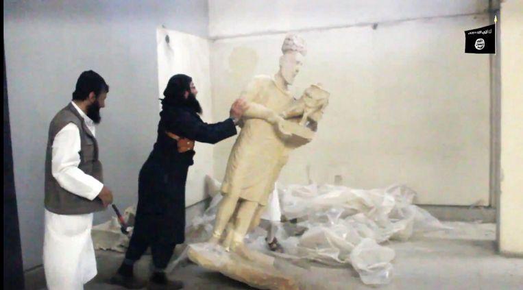 Leden van IS vernielen kunstwerken in een museum in Mosul Beeld AFP