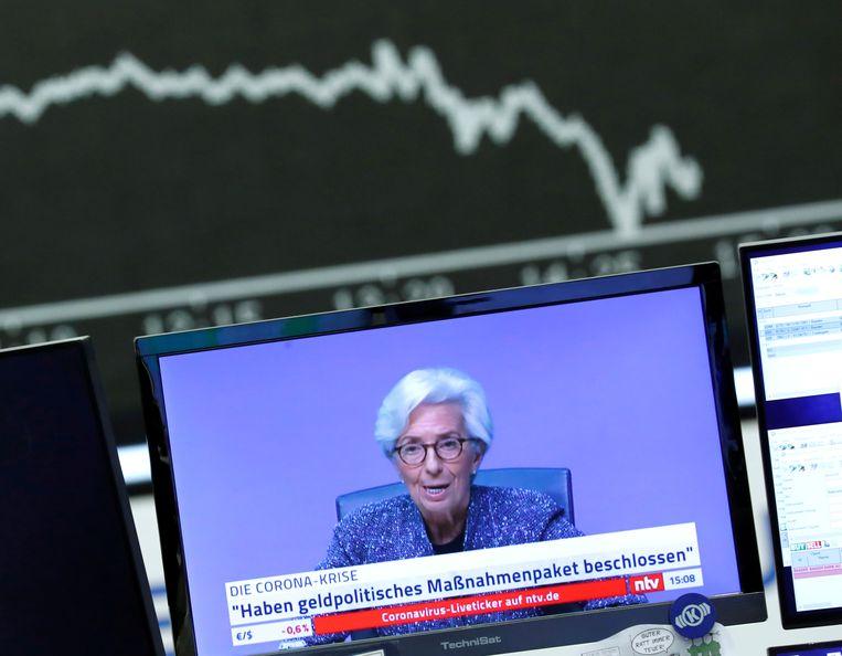 Een scherm op de beurs van Frankfurt toont ECB-president Christine Lagarde, die maatregelen aankondigt om de economische gevolgen van de coronacrisis te beteugelen. Beeld Reuters