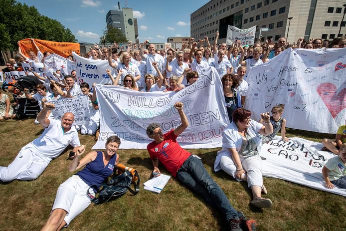 Personeel van het Radboudumc protesteert op het grasveld voor de hoofdingang.