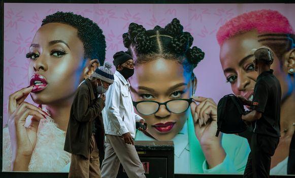 Mensen lopen met mondkapjes op langs een grote advertentie in Soweto, Zuid-Afrika.