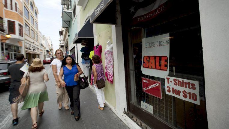 Mensen lopen langs een gesloten winkel in de Puerto Ricaanse stad San Juan. Beeld reuters