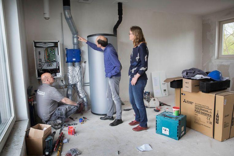 Een installateur sluit in Utrecht een pompinstallatie aan, met rechts de boiler voor 300 liter. Beeld Hollandse Hoogte