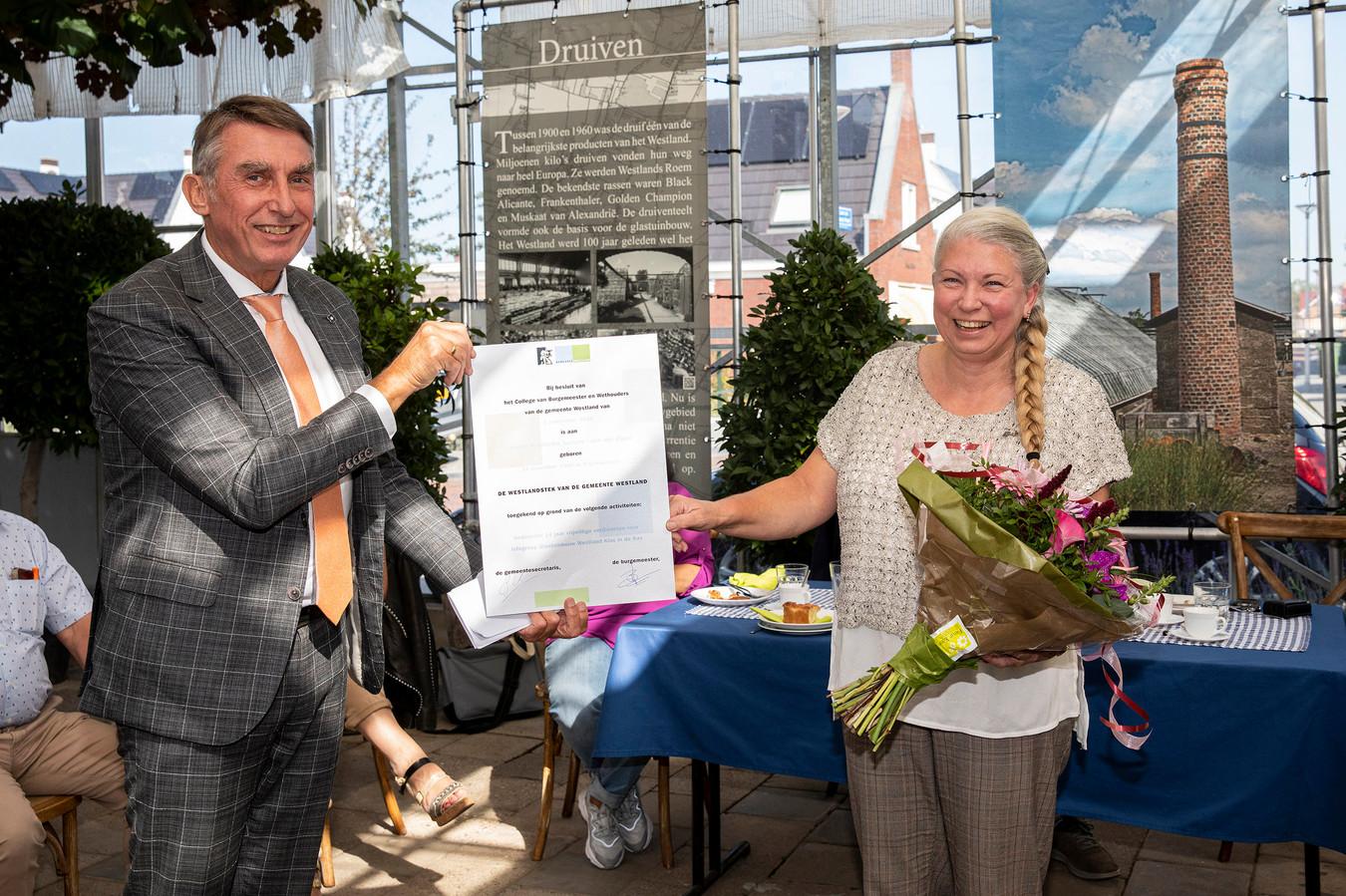 Ivonne Jansen-van der Zwan uit 's-Gravenzande heeft vrijdag een WestlandStek ontvangen van wethouder Albert Abee (glastuinbouw).