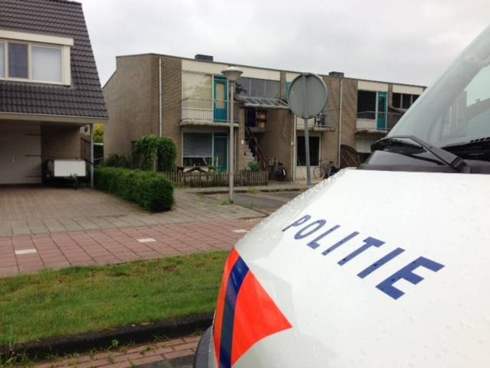 Een politiebusje voor het appartement waar in 2013 het lichaam van de Dalfsenaar werd gevonden.