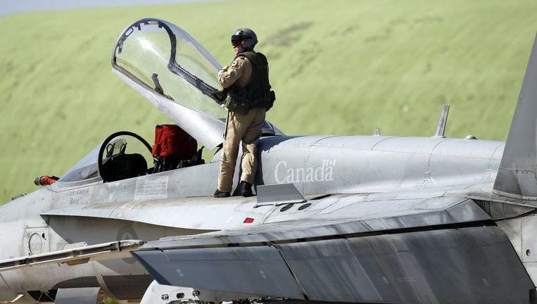 Een piloot staat op een Canadese CF-18A-straaljager op de vliegbasis op Sicilië. Beeld reuters