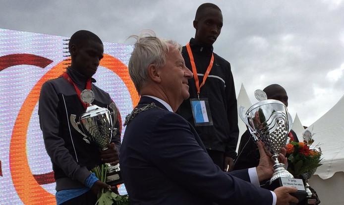 Burgemeester Peter Noordanus reikt de beker uit aan de winnaar van de Tilburg Ten Miles: Rodgers Kwemoi.