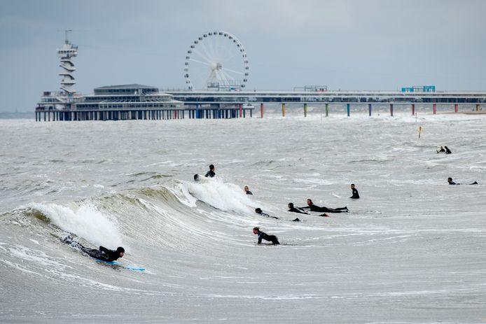 Surfers in zee bij het strand van Scheveningen vandaag. In totaal vijf surfers kwamen ruim een dag eerder bij het Noordelijk Havenhoofd om het leven. Waarschijnlijk werden ze verrast door schuimvorming op de zee.