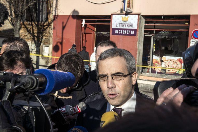 Openbaar aanklager Gregoire Dulin spreekt journalisten, op de achtergrond de kebabzaak waar de explosie plaatsvond. Beeld afp