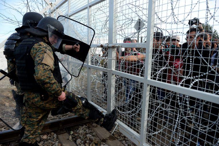 Migranten achter een hek langs de Grieks-Macedonische grens. Macedonië laat alleen nog vluchtelingen uit Syrië en Irak door, net als Servië. Beeld EPA