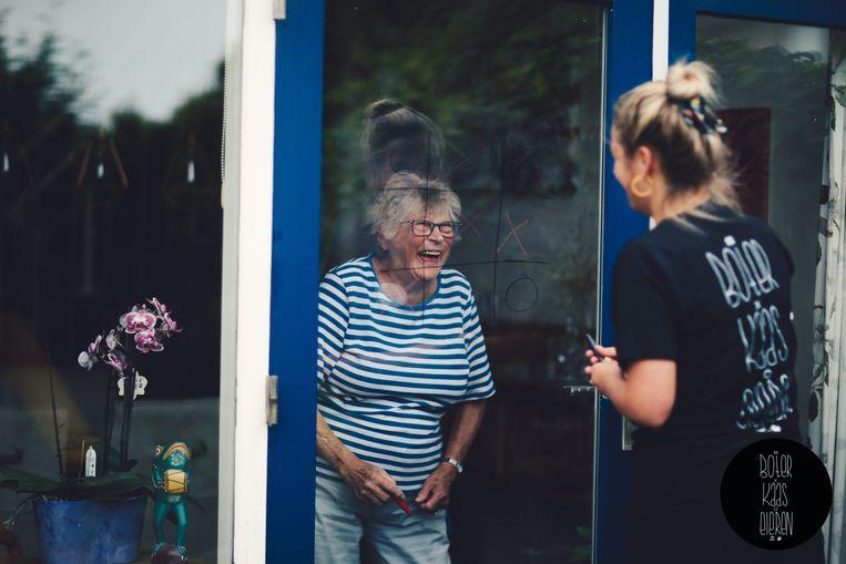 Om de strijd met eenzaamheid aan te gaan roept stichting 10,000 Hours jongeren op raamspelletjes te spelen met ouderen. Beeld 10,000 Hours