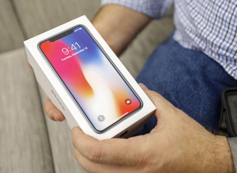 Een consument toont fier zijn iPhone X na aankoop in een winkelcentrum in de Amerikaanse stad Atlanta. De smartphone is bij ons te koop vanaf € 1.159.