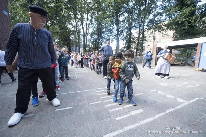 Leerlingen dansen op het vernieuwde schoolplein samen met de Folkoristische dansgroep Hellendoorn