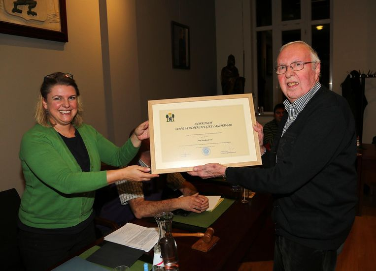 Burgemeester Iris Vander Schelde overhandigt een oorkonde aan Staf Sterkendries.
