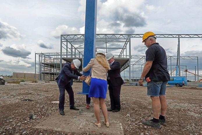 Onder toeziend oog van de uitvoerder zetten wethouder Hans Verbraak (L) en afgevaardigden van Lidl symbolisch de eerste paal vast in de grond in Roosendaal.