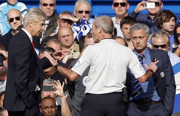 Wenger (links) en Mourinho (rechts) luisteren naar scheidsrechter Martin Atkinson. Beeld reuters