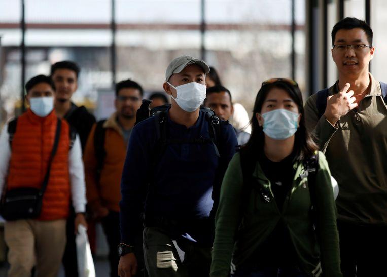 Reizigers met maskers arriveren op het vliegveld van Kathmandu, Nepal. Beeld Reuters