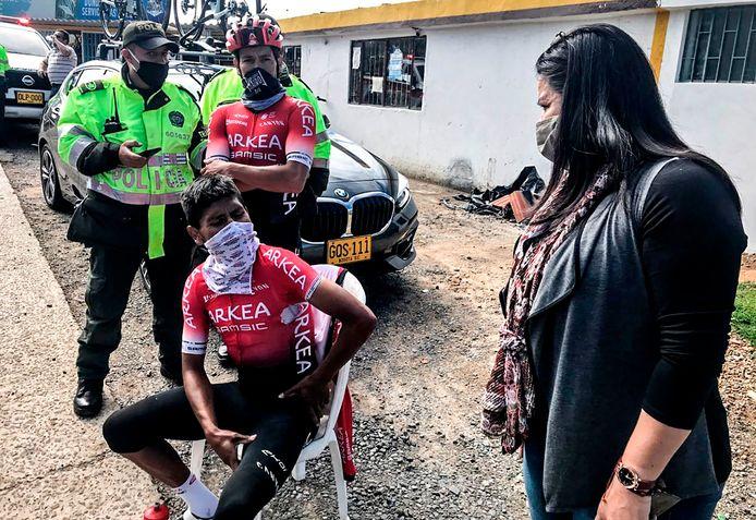 Nairo Quintana moet even bijkomen nadat hij is aangereden door een auto. Op de achtergrond komt lokale politie poolshoogte nemen.