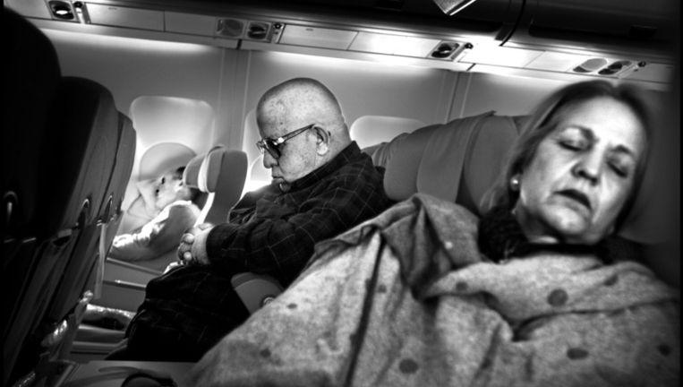 Passagiers slapen tijdens een lange vlucht © Joost van den Broek/ de Volkskrant Beeld