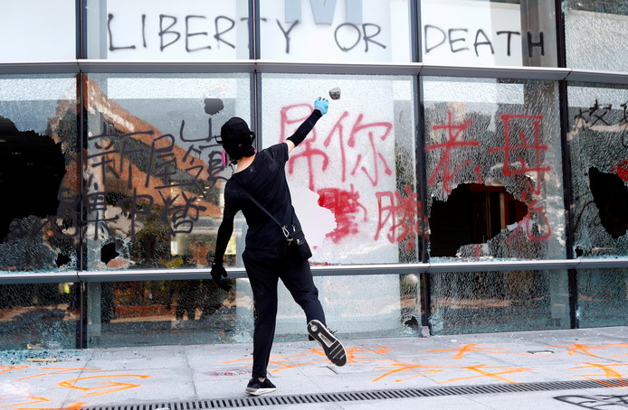 Het geweld laait op. Een demonstrant gooit een ruit in van een campusgebouw op de Polytechnic University in Hongkong.