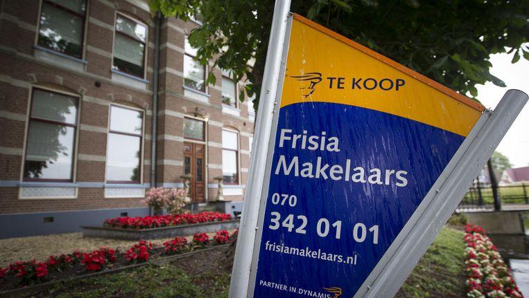 Een verkoopbord voor een huis dat te koop staat. Beeld anp