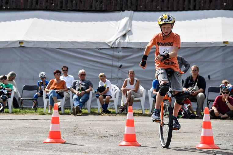 Een jongen legt een parcours slalom af op zijn eenwieler.