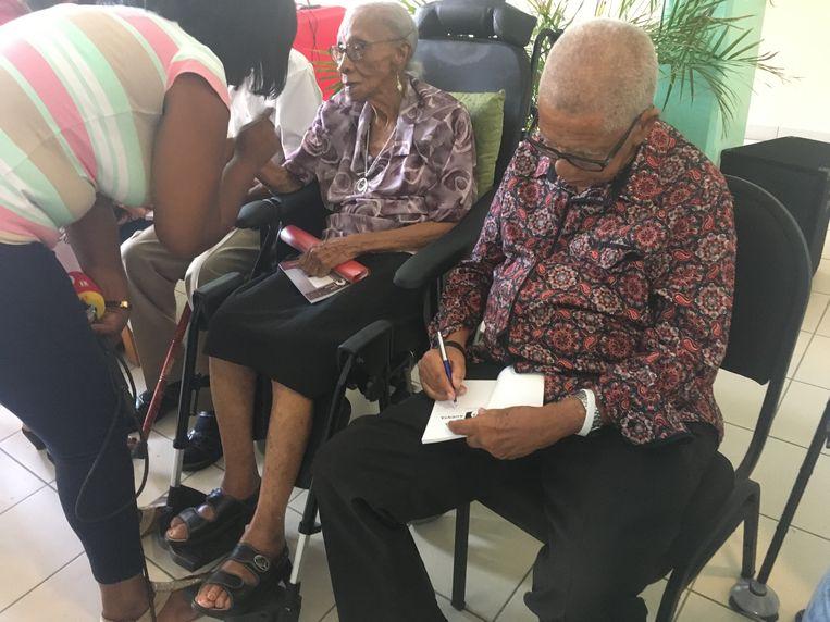 Een oudere signeert zijn werk in Willemstad. Beeld null