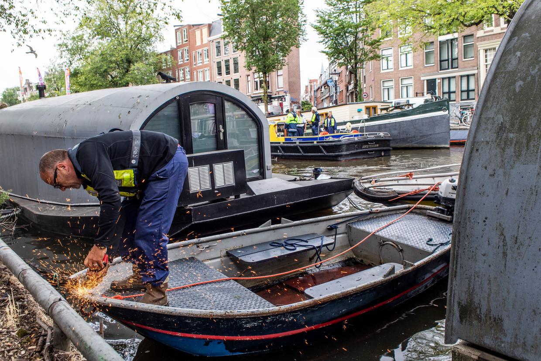 Medewerkers van Waternet gebruiken slijptollen om boten zonder uitzonderingsvignet los te maken van de kade. Beeld Lin Woldendorp