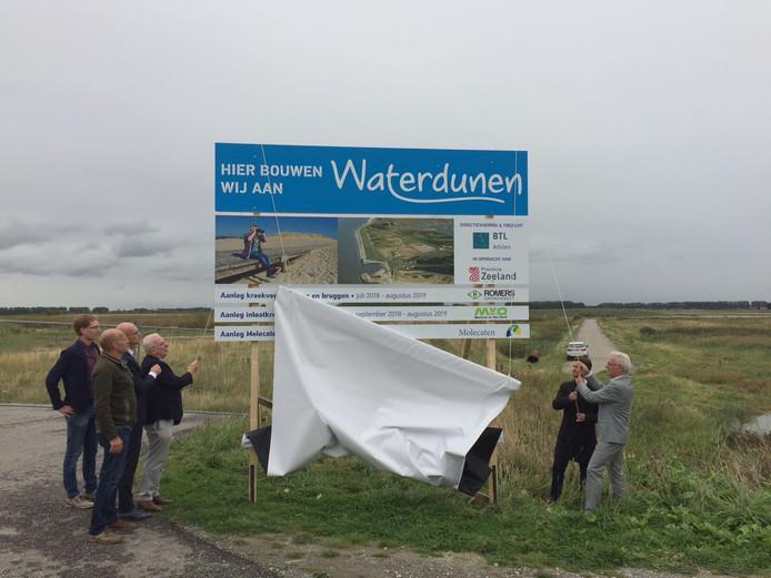 Gedeputeerde Ben de Reu (r) onthult het bouwbord van Waterdunen. Dat staat ter hoogte van 't  Killetje.