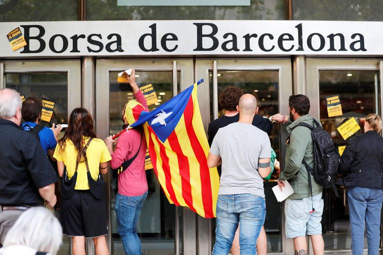 Catalaanse separatisten plakken stickers met onafhankelijkheidsleuzen op het beursgebouw van Barcelona.  Beeld EPA