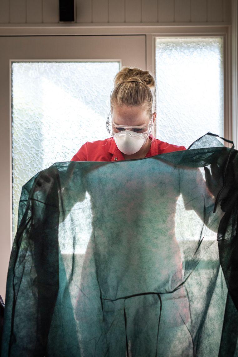 Bij een coronapatiënt kleedt Inge zich volgens een vaste procedure aan. Eerst de handschoenen aan. Daarna een nieuw schort of het schort dat al bij de patiënt hangt (wordt maximaal 3 keer gebruikt). Een mondkapje op en een veiligheidsbril. Beeld Linelle Deunk