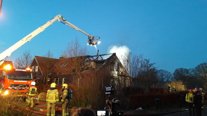 Met een hoogwerker bestrijdt de brandweer het vuur.