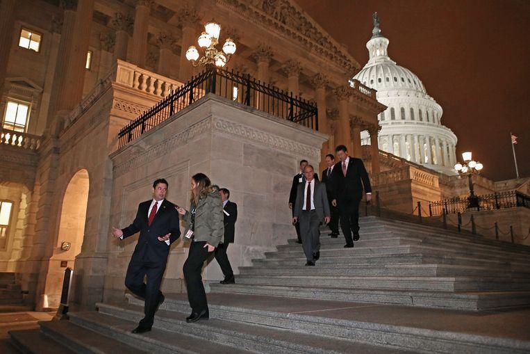 Leden van het Huis van Afgevaardigden verlaten het Capitool in Washington. Beeld getty