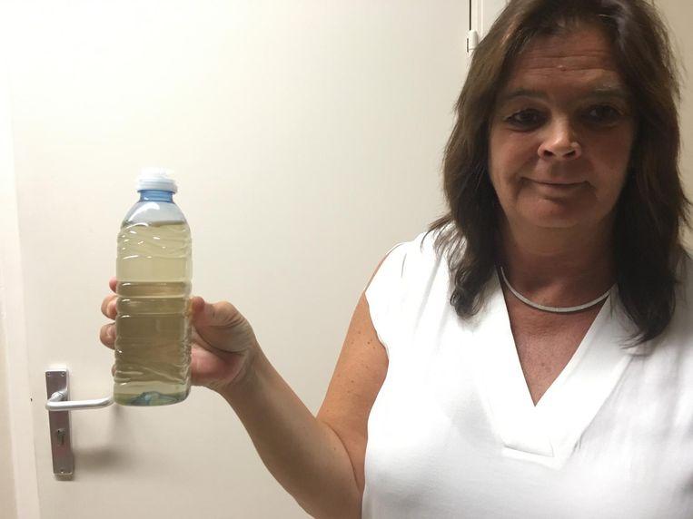 Sandra Van Renterghem toont hoe vuil het drinkwater van Oostakker is.