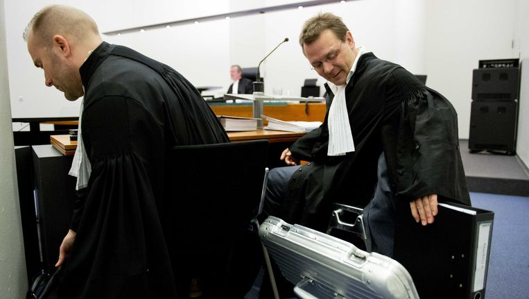 De advocaat van Sabir K., Andre Seebregts (R), neemt het dossier ter hand in de rechtbank van Den Haag. Beeld ANP
