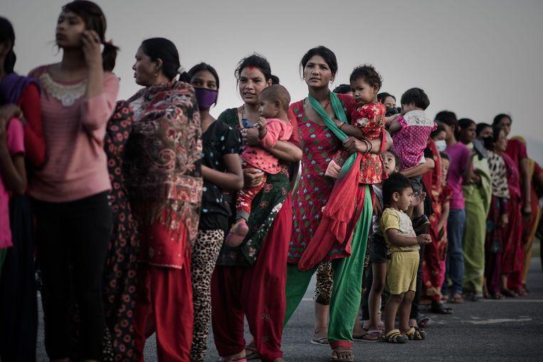 Overlevenden van de aardbeving staan in de rij voor voedselverstrekking in Kathmandu. Beeld afp