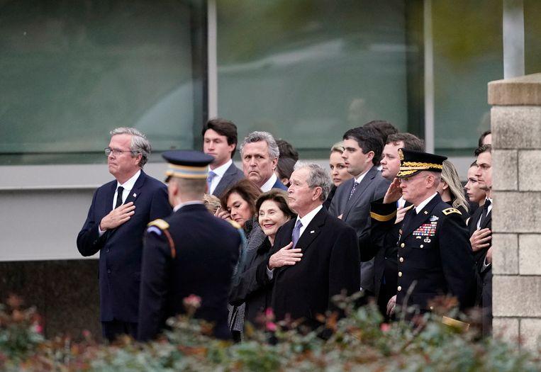 De familie Bush kijkt toe hoe de kist van hun (groot)vader wordt weggedragen door een erewacht.