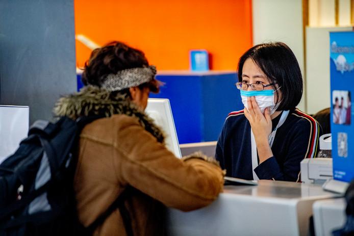 Personeel en reizigers op Schiphol met mondkapjes op ter bescherming van het coronavirus.