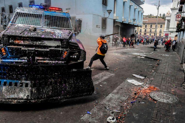 Een demonstrant bewerkt woensdag  een bepantserde politieauto tijdens rellen in Quito.  Beeld AFP