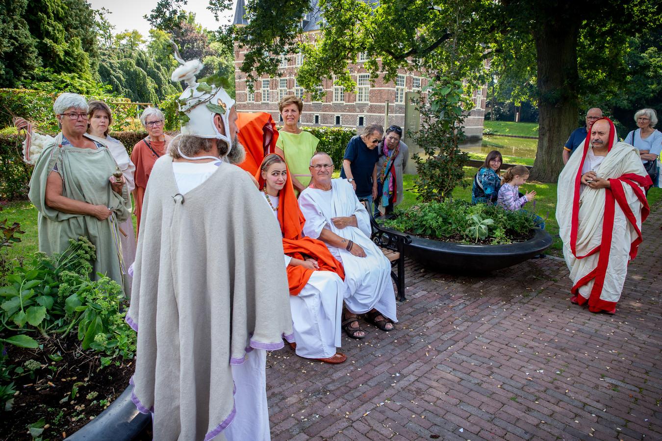 Het echtpaar in het midden, met links, op de rug gezien, de flamen Dialis.
